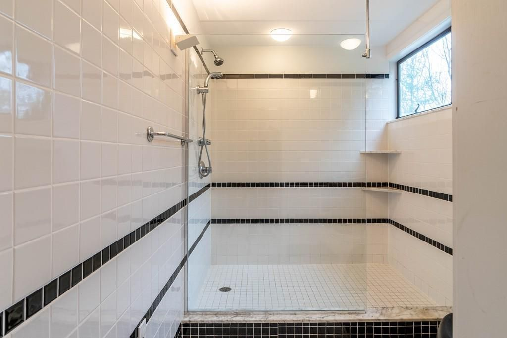A large shower in a bathroom, with nothing separating it.