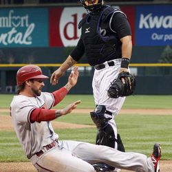 Arizona Diamondbacks' Ryan Roberts, front, slides safely across home plate as he scores on a single by Chris Young while Colorado Rockies catcher Ramon Hernandez looks on in the first inning of a baseball game in Denver on Saturday, April 14, 2012.