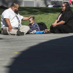 Curtis Sillito touches his daughter Camyleh's head as he and his wife Simone sit on the ground listening to the Saturday afternoon session of the 183rd Semiannual General Conference for the Church of Jesus Christ of Latter-day Saints Saturday, Oct. 5, 2013 inside the Conference Center.