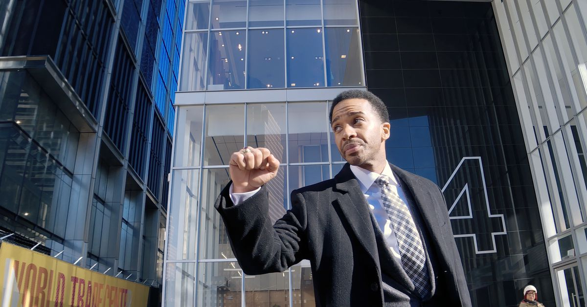 A man leaves a building and raises a fist.