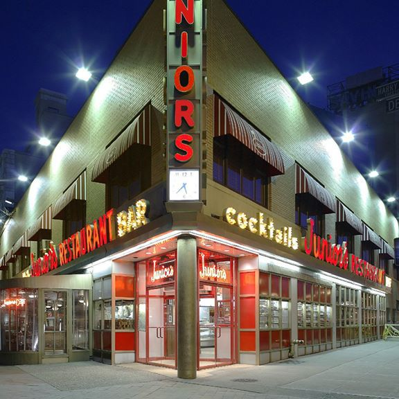 The exterior of Junior's with neon signage