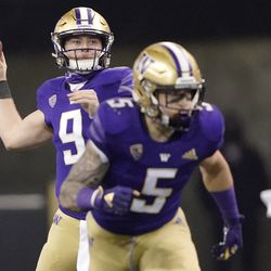Washington quarterback Dylan Morris, left, drops to pass as running back Sean McGrew (5) takes off from the line of scrimmage during the second half of an NCAA college football game against Utah, Saturday, Nov. 28, 2020, in Seattle.