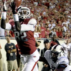 Arkansas wide receiver Mekale McKay (82) catches a 13-yard touchdown pass as he eludes Louisiana Monroe cornerback Otis Peterson, right, during the third quarter of an NCAA college football game in Little Rock, Ark., Saturday, Sept. 8, 2012.