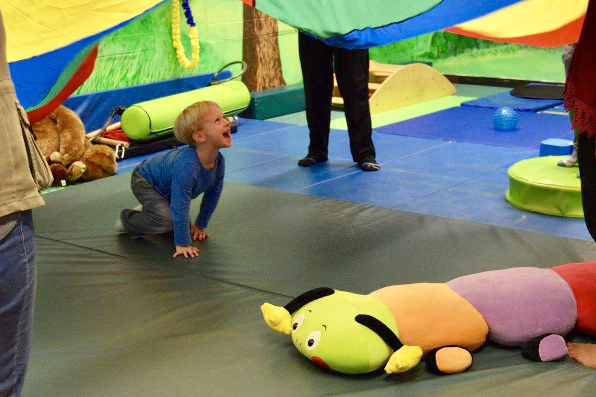 A child plays under a colorful parachute at the SUNY Cortland Sensory Integration/Motor Sensory (SIMS) Movement Exploration Center, where undergraduates training to become physical education teachers have the opportunity to work one-on-one with children of all abilities.