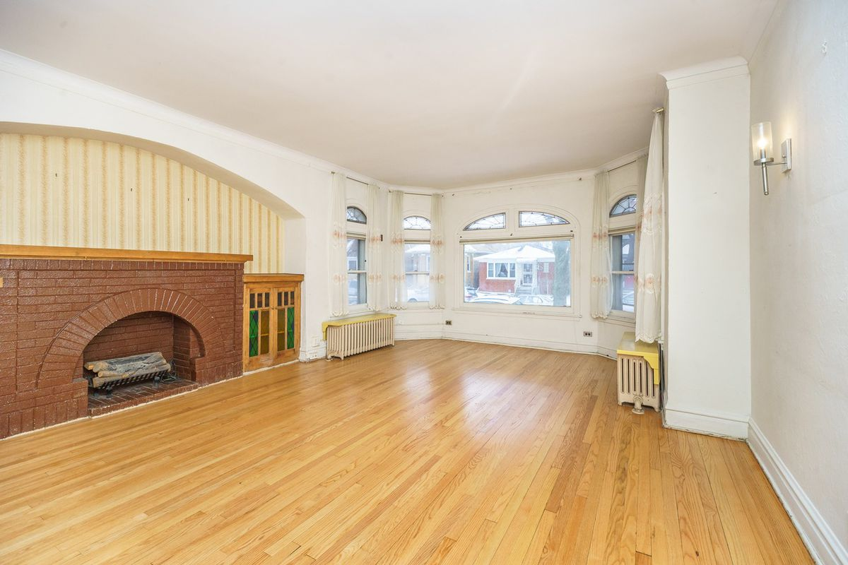 A fireplace with painted brick and an arched front. There are front bay windows.