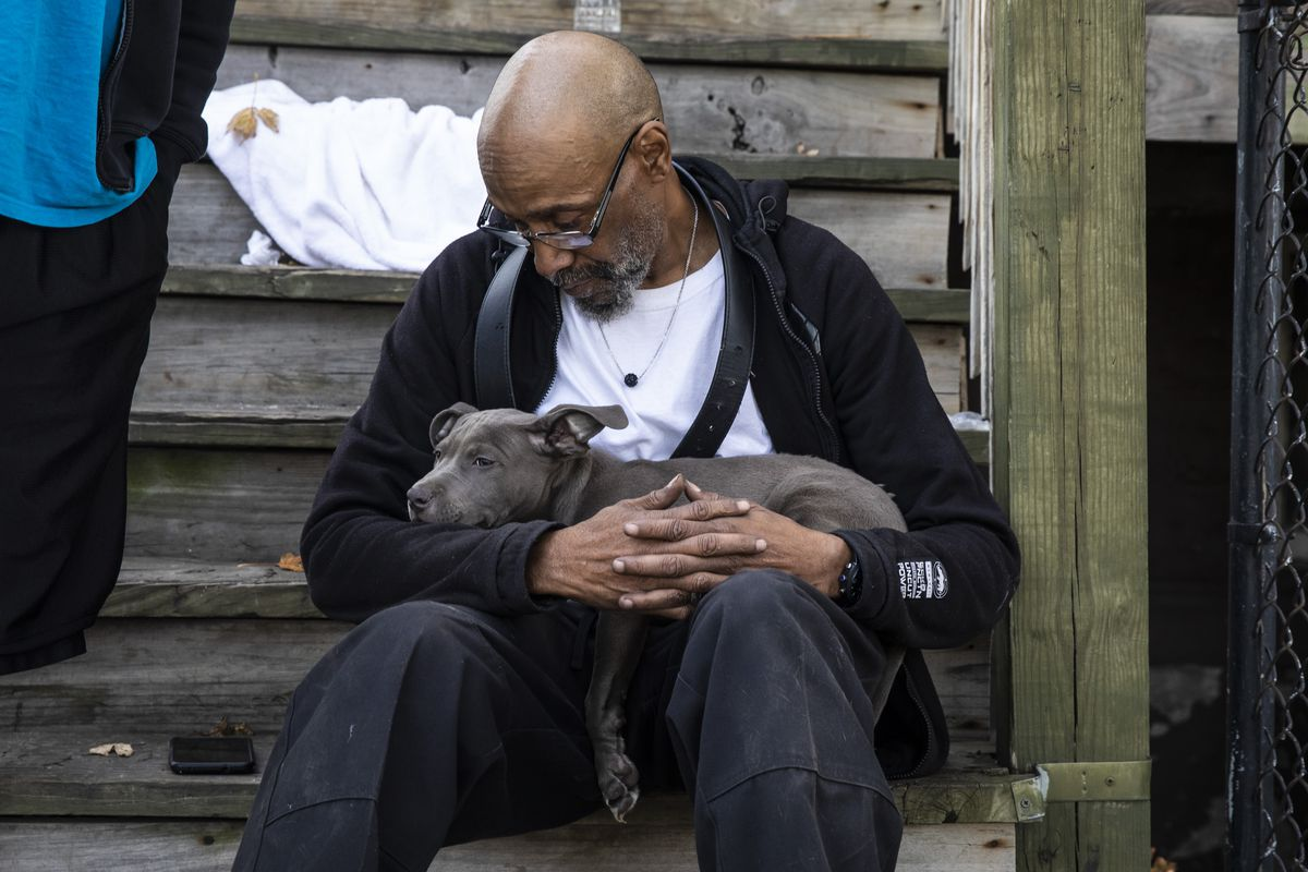 Bernard Stratton sits on a neighbor's front porch and cradles his puppy with burn injuries after the dog was rescued from his burning home early Thursday in the 4900 block of South Princeton Avenue in Fuller Park on the South Side.