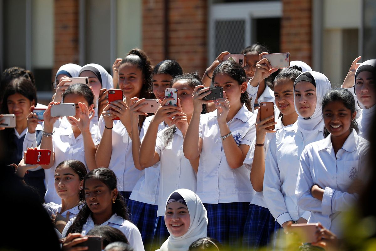 A group of young women hold their phones up to take pictures of an event.