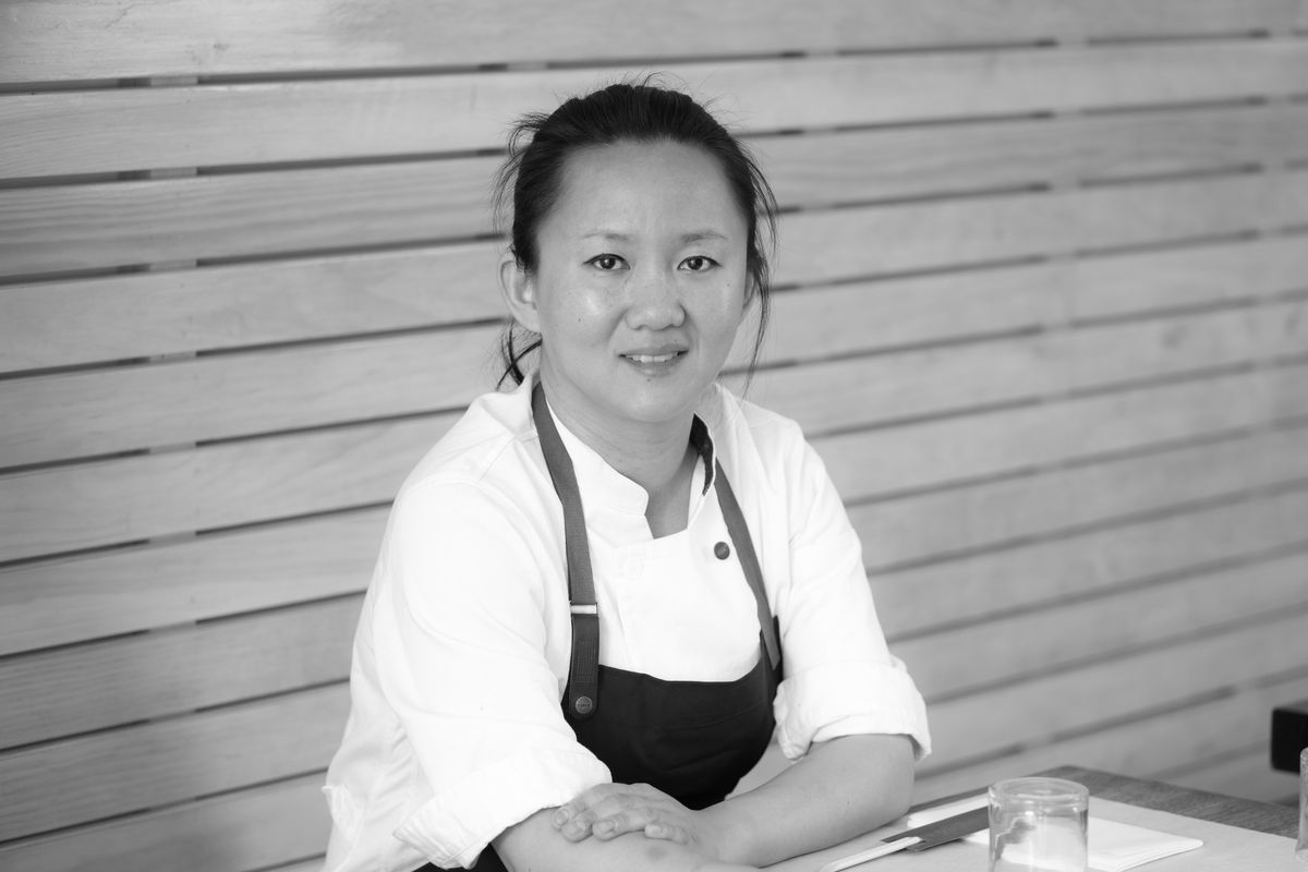 Simone Tong sits at a table with her hair pulled back and an apron on