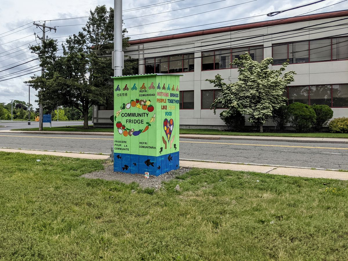 A bright green pantry sits alongside a road. It's painted with fruits, vegetables, and words indicating that it's a community fridge.
