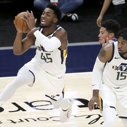 Utah Jazz guard Donovan Mitchell (45) shoots in front of Utah Jazz center Derrick Favors (15) during a preseason NBA game at the Vivint Smart Home Arena in Salt Lake City on Monday, Dec. 14, 2020. The Jazz beat the Suns 111-92.