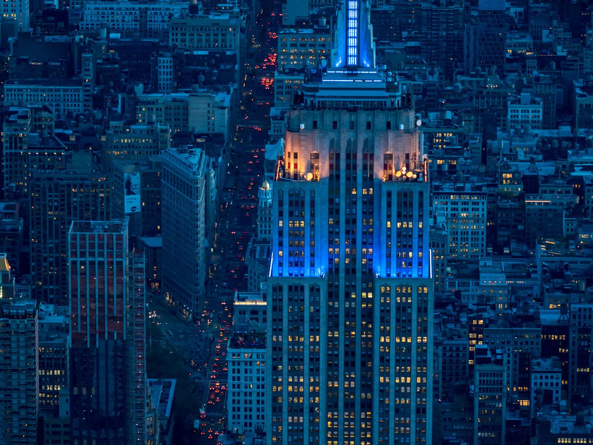 The top of the Empire State Building in New York City. The skyscraper has a spire on top. It is evening and the building is illuminated in blue light. There are many city buildings surrounding the skyscraper.