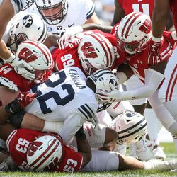 Brigham Young Cougars running back Squally Canada (22) is shut down on a run by Wisconsin Badgers defense at LaVell Edwards Stadium in Provo on Saturday, Sept. 16, 2017.