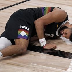 Denver Nuggets' Jamal Murray (27) lays on the court after a collision with Utah Jazz's Joe Ingles (2) during the first half an NBA first round playoff basketball game, Tuesday, Sept. 1, 2020, in Lake Buena Vista, Fla.