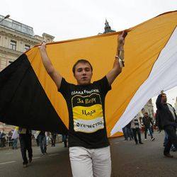 """Monarchists carry an old Russian imperial flag as they march to a protest rally in Moscow, Saturday, Sept. 15, 2012. Thousands of protesters marched across downtown Moscow on Saturday in the first major rally in three months against President Vladimir Putin, while defying the Kremlin's ongoing efforts to crackdown on opposition. T-shirt reads the old Russian imperial slogan """"Glory to Russia. For the faith, the czar and the fatherland."""""""
