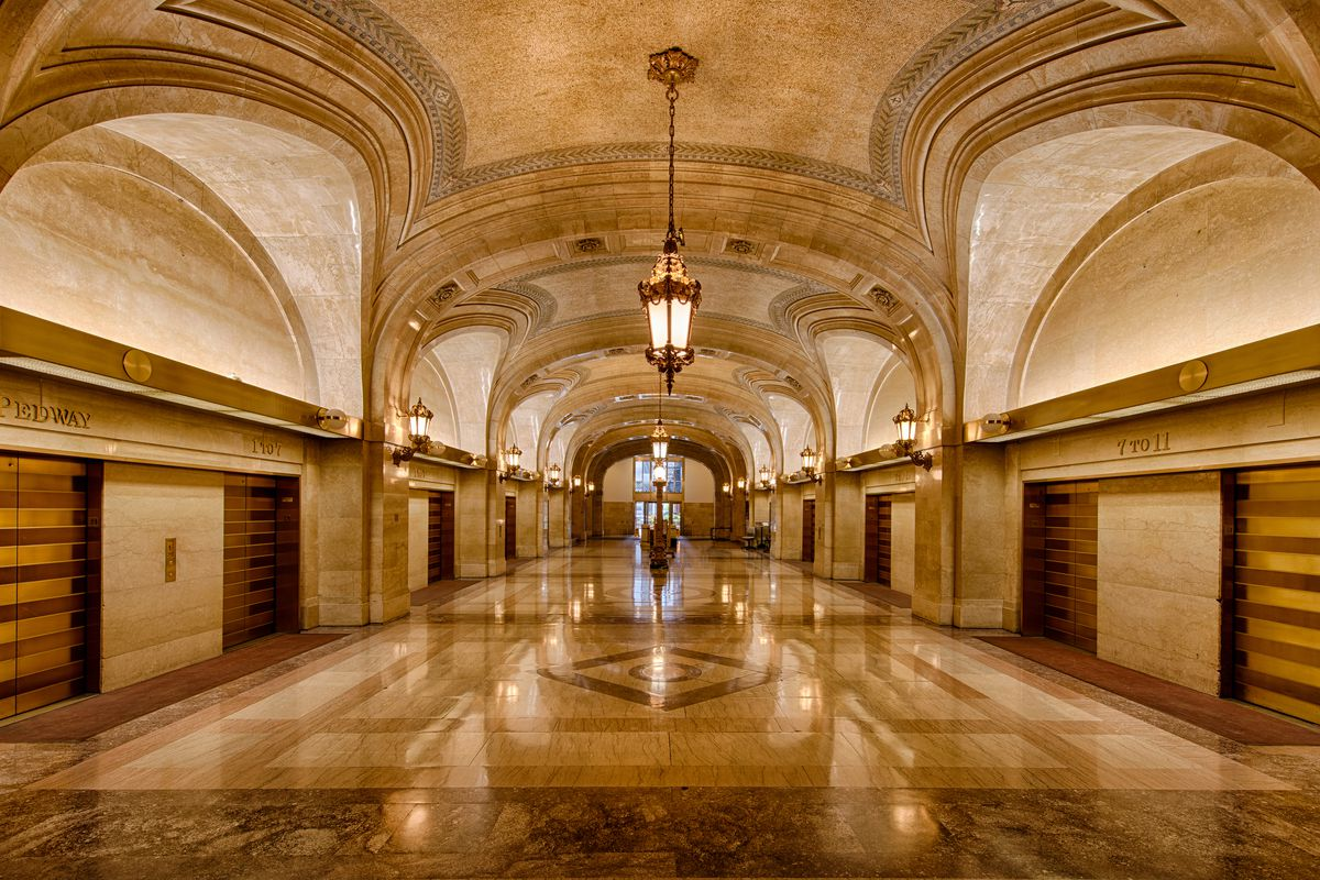 A grand hall and gold elevator banks on either side. Intricate, muted mosaic tiles and a domed ceiling. Chicago city hall.