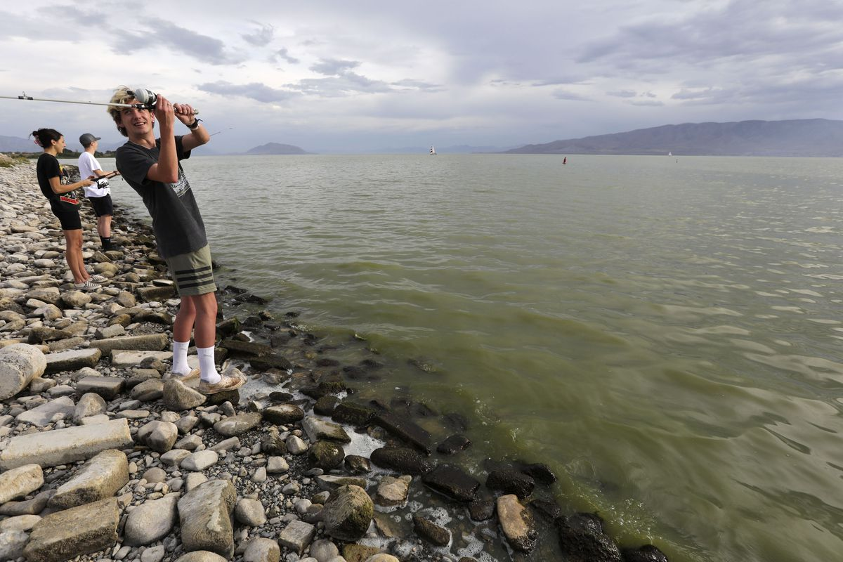 Brian Schulz fishes in Utah Lake, where there are algal blooms, at the Lindon Marina in Vineyard on Monday, July 19, 2021. Marli Shaw and Tyler Penrod fish behind him.