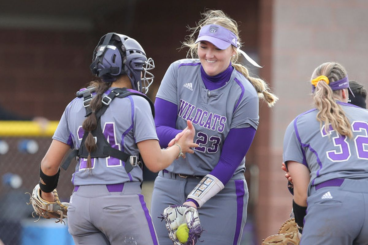 Lauren Hoe and Addie Jensen give each other high fives in the game against Southern Utah. Hoe had a grand slam in the second game to give the Wildcats the win.
