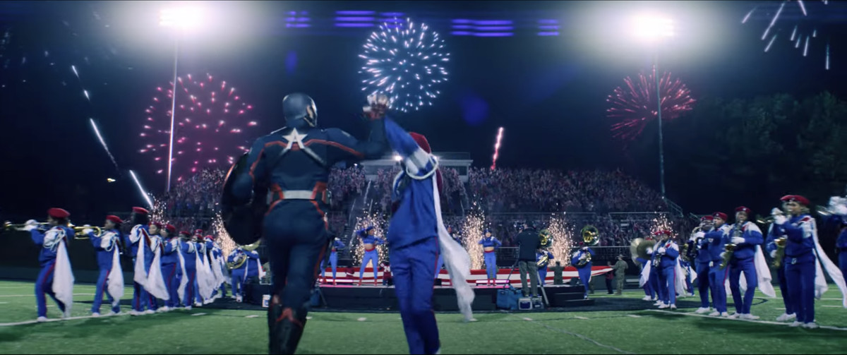 USAgent high fives the drum major as he runs out to the field during halftime at a football game in Falcon and the Winter Soldier.