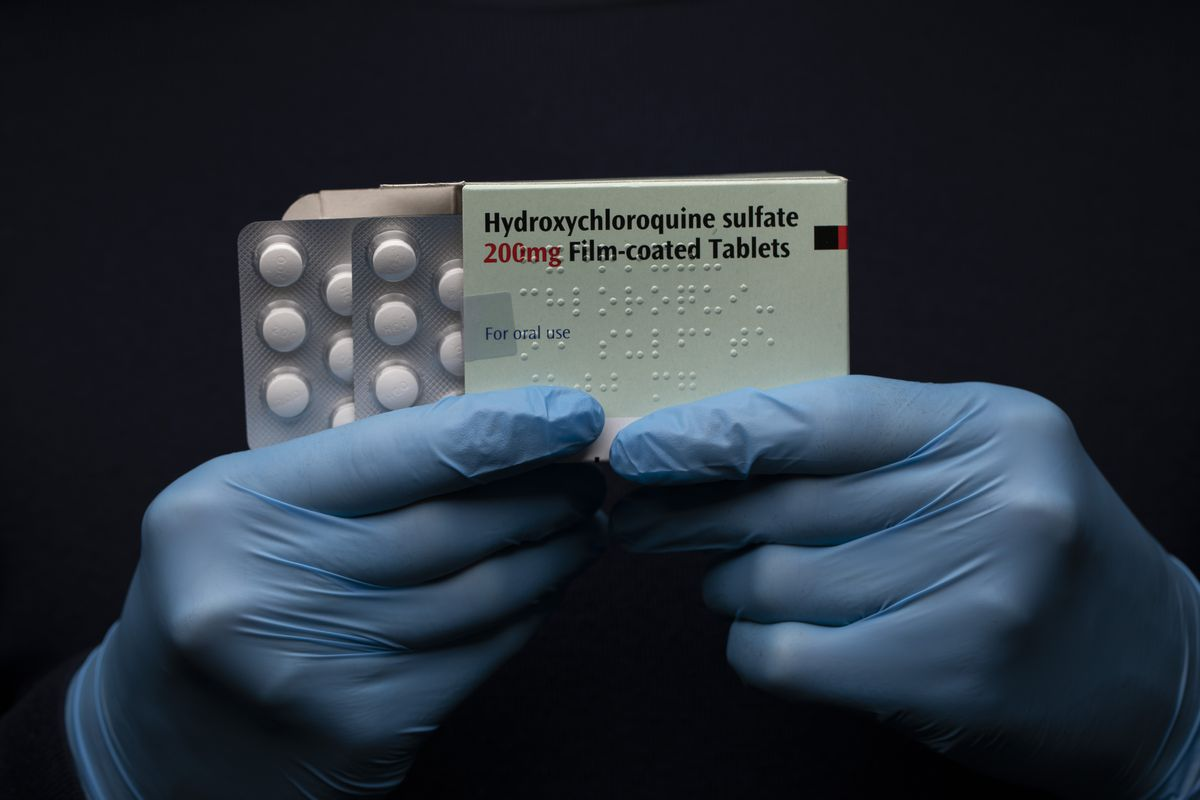 Hands holding up Hydroxychloroquine Sulfate medication.