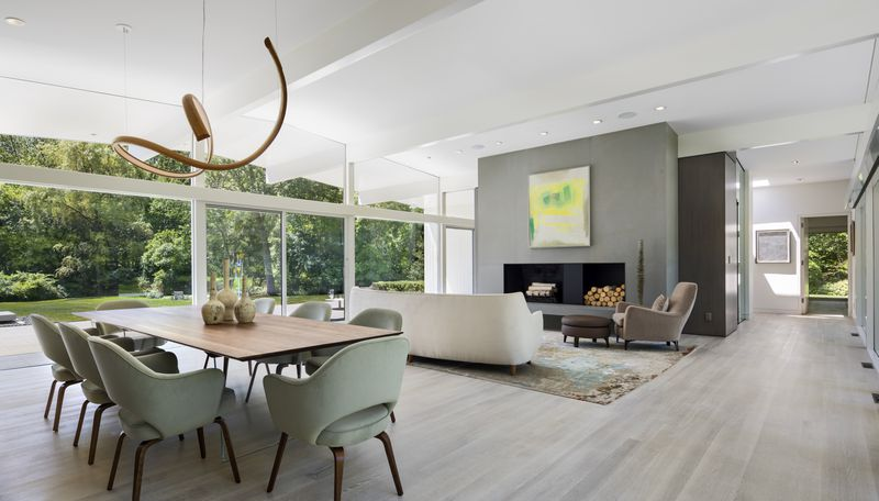A living room and dining area has a table with chairs and a large fireplace.
