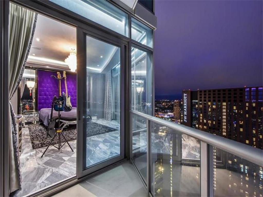 Exterior shot of bedroom with purple headboard, two guitars staged in front, and dusk sky from balcony