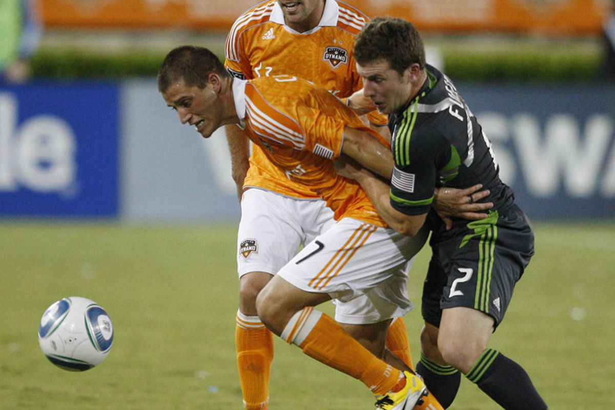 HOUSTON - JULY 30:  Colin Clark #7 of the Houston Dynamo holds off Mike Fucito #2 of the Seattle Sounders as Hunter Freeman #21 looks on at Robertson Stadium on July 30, 2011 in Houston, Texas.  (Photo by Bob Levey/Getty Images)