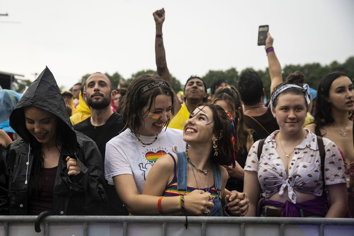 Zoe Meier, 19, of Mount Prospect, dances with her girlfriend, 20-year-old Stella Gross Shafer, in the rain Saturday afternoon during Pride in the Park in Grant Park.