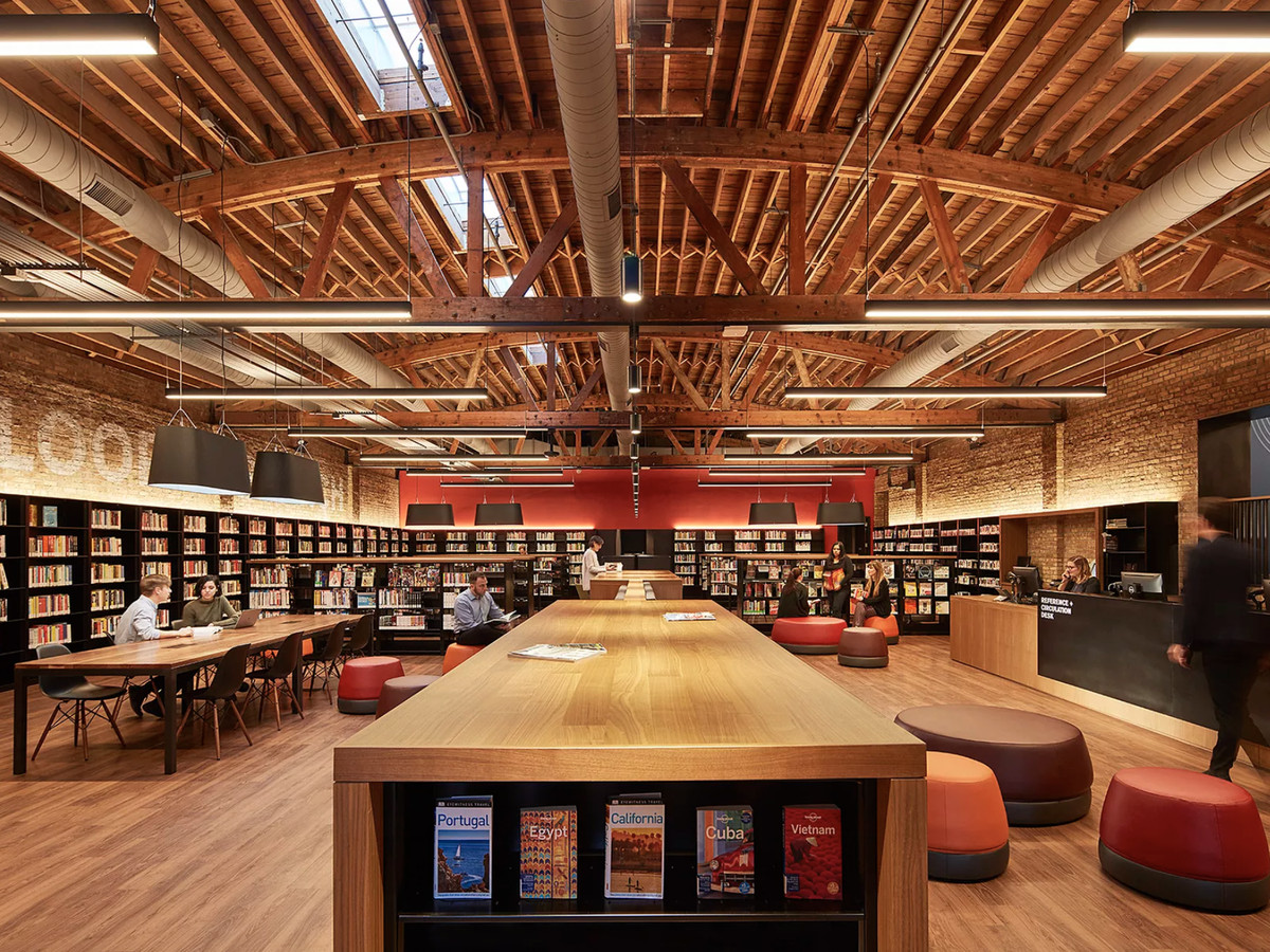 A bow-truss building with exposed ceiling timbers filled with bookshelves, large tables, and padded stools.