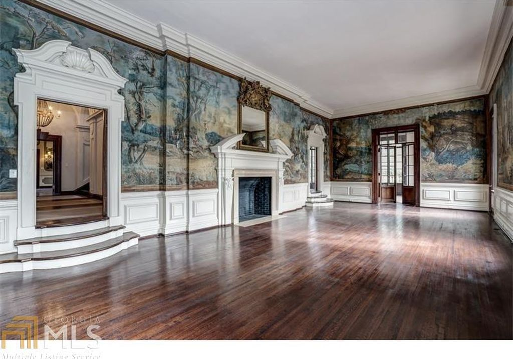A large room with dark wood floors and soaring ceilings, with intricately painted pastoral murals and a large, grand fireplace.