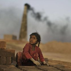 In this Tuesday, April 3, 2012 photo, Pakistani Naginah Sadiq, 5, who works at a brick factory and earns 250 Rupees ($2 .77 cents) per day according to her father, is seen arranging the bricks, on the outskirts of Islamabad, Pakistan. Clutching photocopied ID cards in bony fingers, a roomful of Pakistan's poorest women sit on gray plastic chairs and wait in silence for something many have never experienced: a little bit of help from the government. It comes in the form of a debit card that is topped up with the equivalent of 30 dollars every three months.