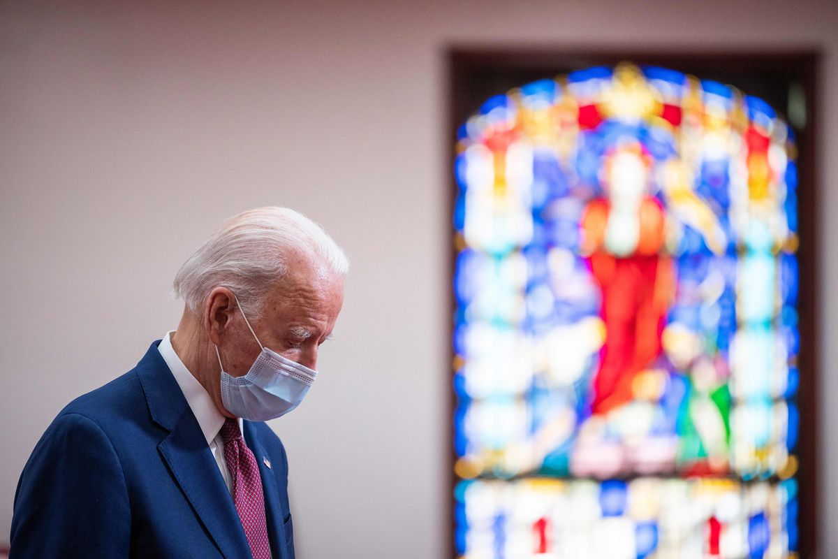 Joe Biden bows his head in prayer in front of a stained glass window.