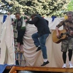 """While picnicking from left, Jacques (Daniel Joseph Anderson), Silvius (Greg Larsen), Charles the Wrestler (Levticus Brown), Oliver (Kyle Oram) and Duke Frederick (Dan Whiting) sing and dance to """"Big Rock Candy Mountain."""""""