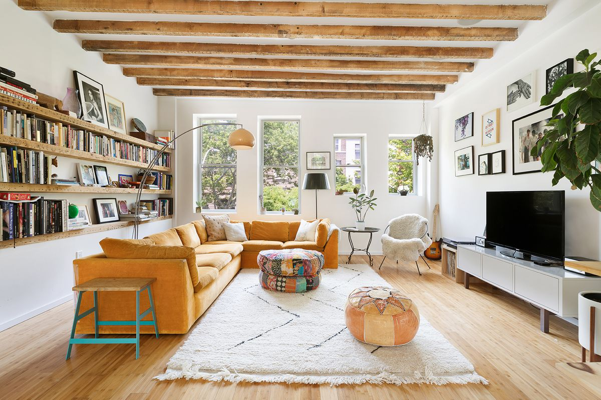 A living area with hardwood floors, high ceilings, and wood beams in its ceilings.