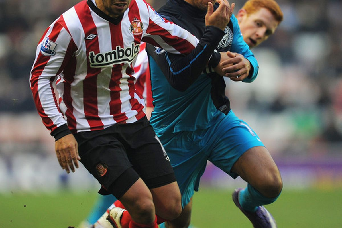 Kieran Richardson (L) of Sunderland in action with Theo Walcott of Arsenal during the Barclays Premier League match between Sunderland and Arsenal at the Stadium of Light.