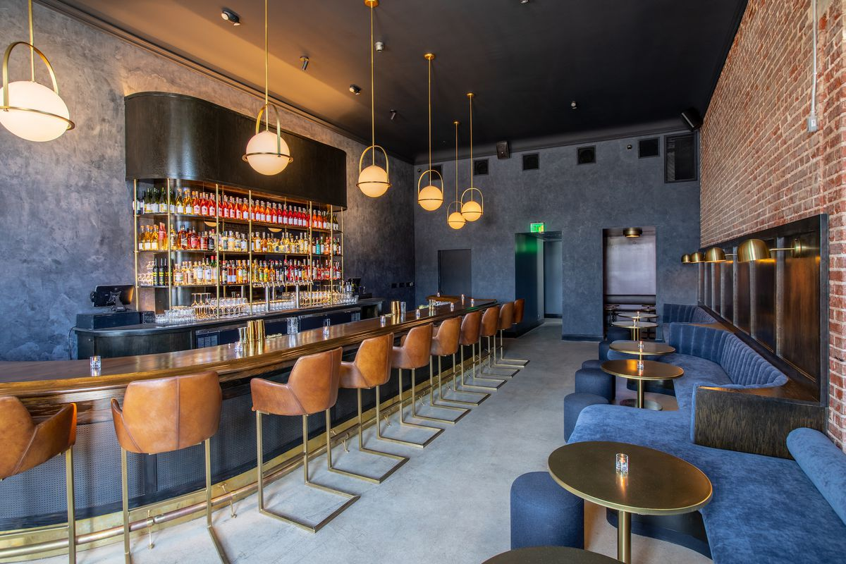 An angled look at a new art deco bar with pendant lights and a long bar and blue seats.