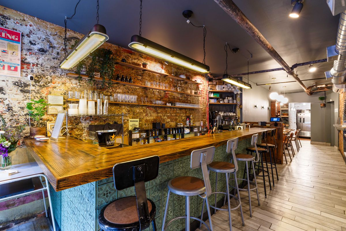 Bar stools are lined up at counter with overhead lights and a selection of liquors on the wall