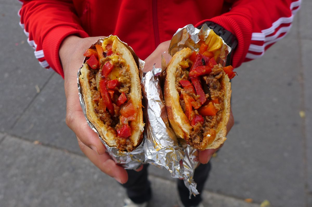A pair of hands holds two sandwich halves wrapped in aluminum foil, with red bell peppers visible.