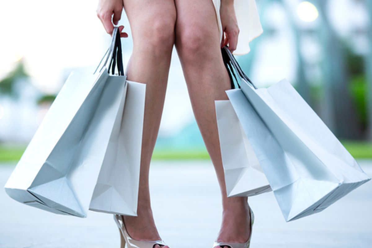 """Image via <a href=""""http://www.shutterstock.com/pic-117276970/stock-photo-tired-woman-after-a-shopping-spree-holding-bags.html"""">Andresr</a>/Shutterstock"""