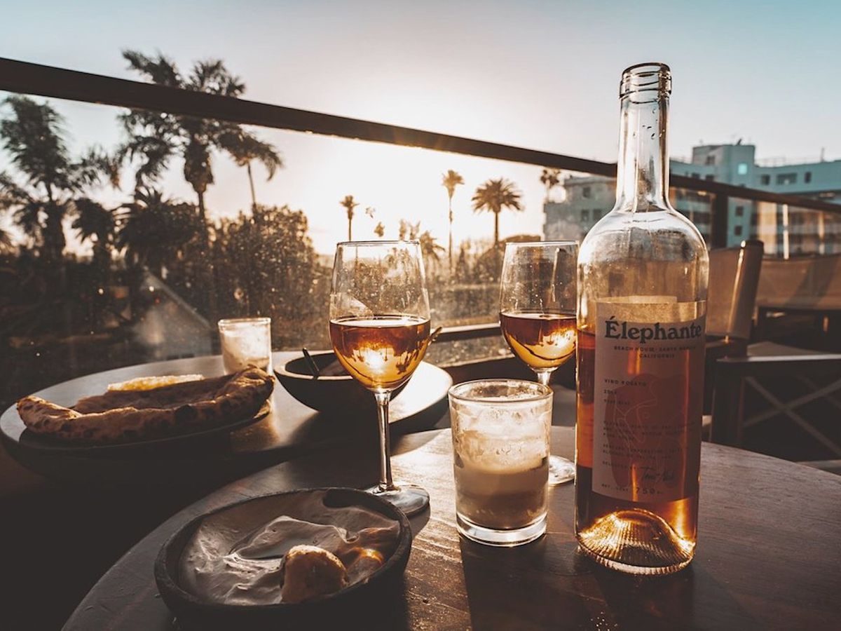 Glass bottle of alcohol with two wine glasses on a rooftop