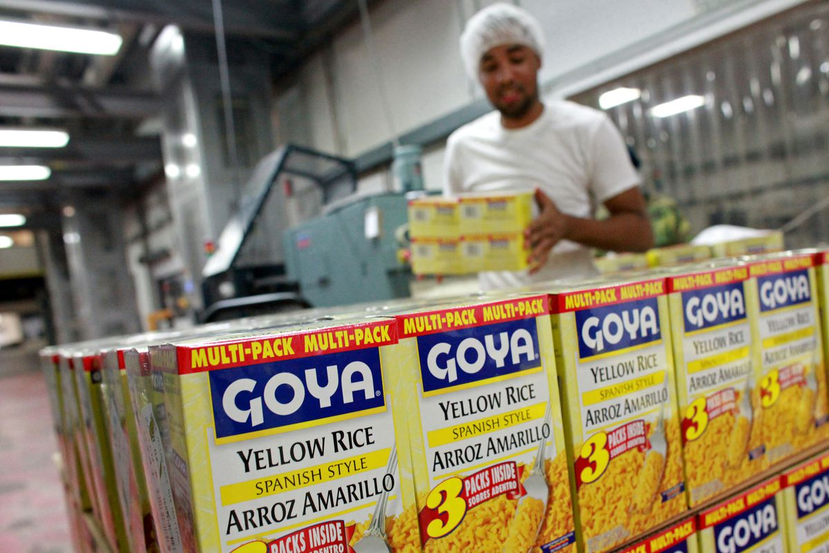"A Black man in a hair net stacks yellow and blue boxes of Goya's ""Spanish Style"" yellow rice on a pallet."
