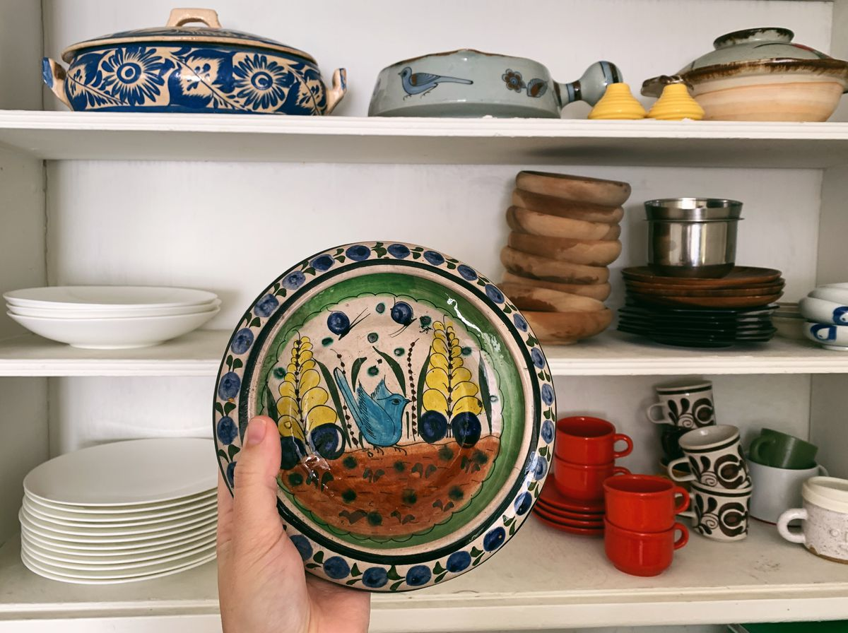 A hand holds a ceramic, painted plate with a blue bird in the middle. In the background is a three-shelf cabinet holding a stack of white plates, wooden bowls, red coffee mugs, and various other kitchenware.