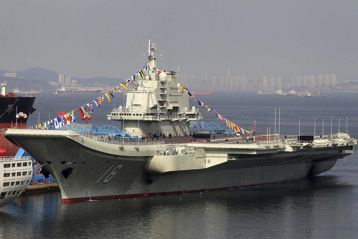 China's as yet unnamed aircraft carrier is decorated with coloured flags at a shipyard in Dalian in northeast China's Liaoning province Monday Sept. 24, 2012. The carrier, built on former Ukrainian vessel Varyag, was delivered to the Chinese navy Sunday S