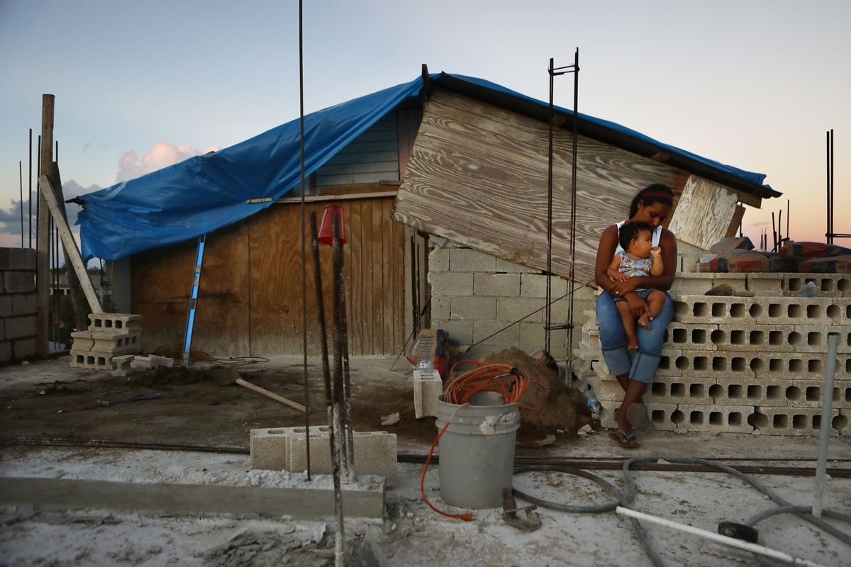 Mother Isamar holds her baby Saniel, nine months old, at their makeshift home after Hurricane Maria, on December 23, 2017 in San Isidro, Puerto Rico.