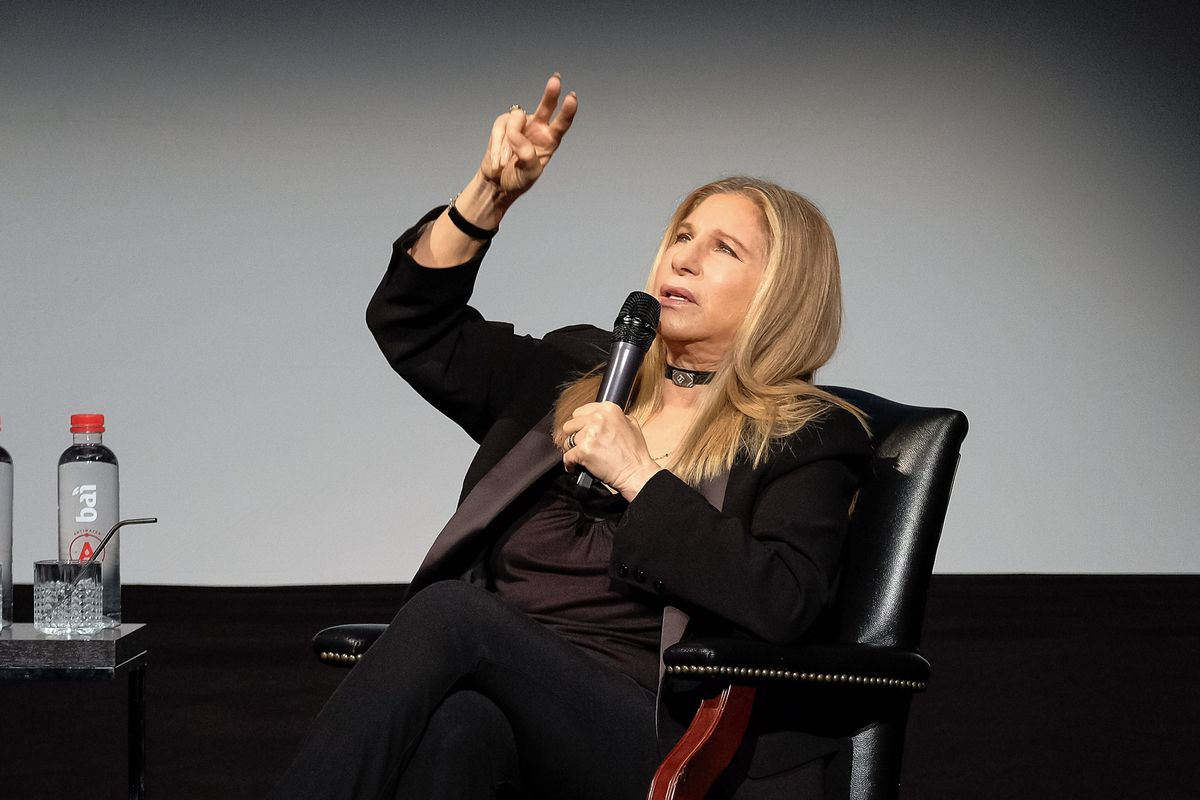 Barbra Streisand sitting in a chair onstage at a conference and speaking into a handheld microphone.