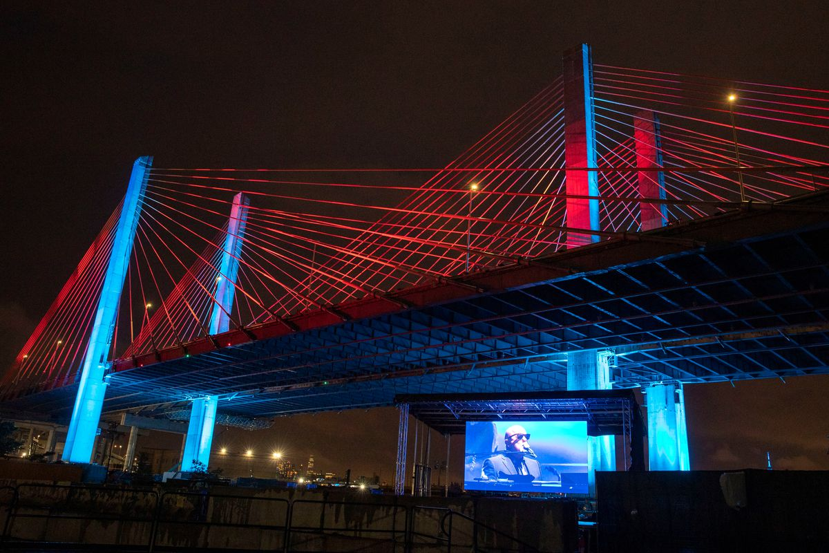 A suspension bridge with steel cables at nighttime. There is a screen under the bridge showing a live performance from a piano player.