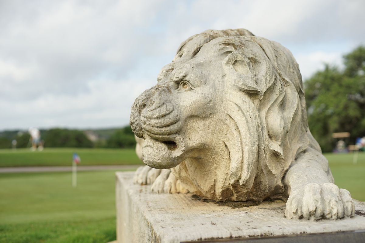 Lion statue with golf course in background