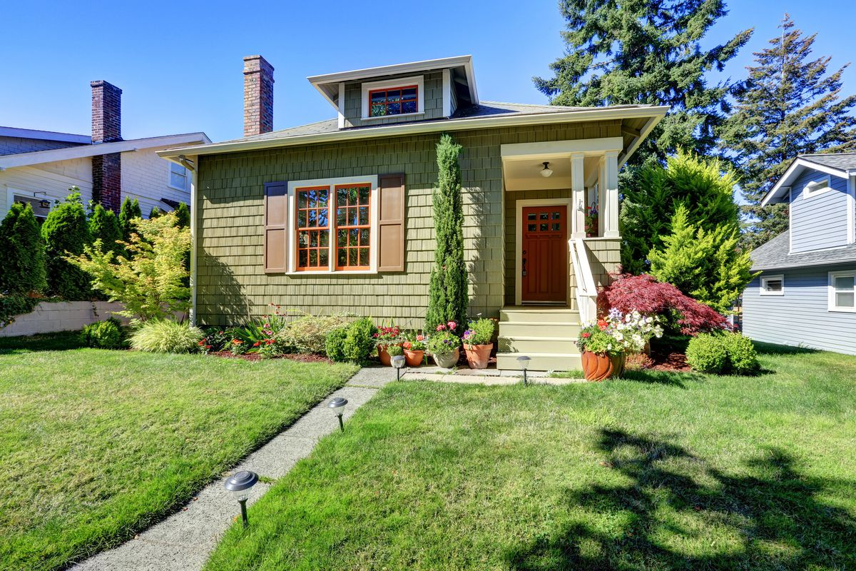 A dark green craftsman style home with large green front yard and several potted plants.