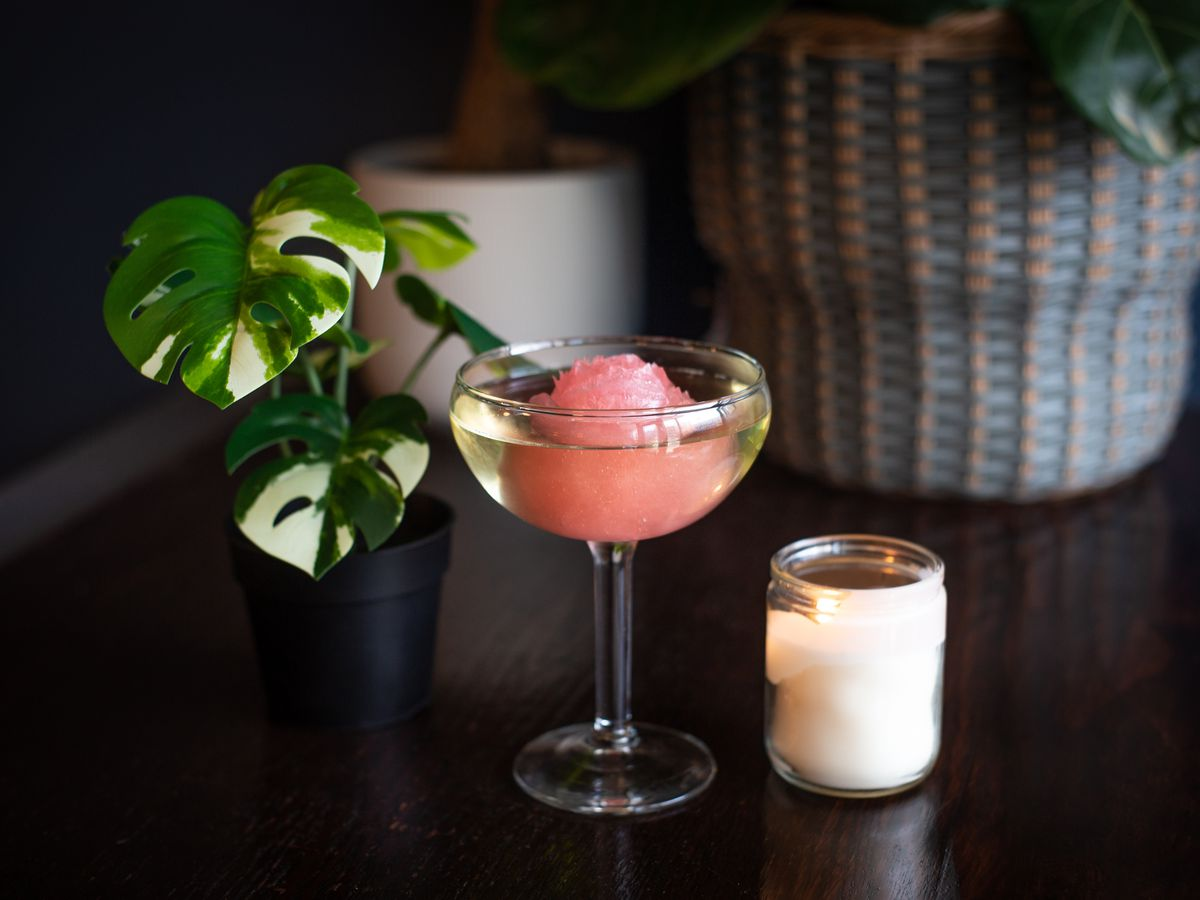 A coupe glass filled with yellow prosecco and a pink rose ice cube sits on a dark table with green plants in the background and a small white candle to the right of the drink.