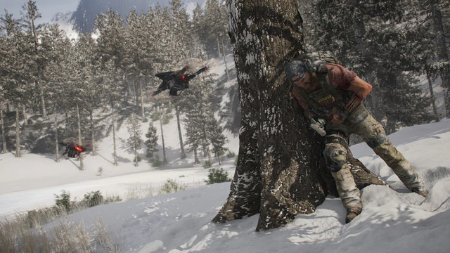A soldier leans behind a tree on a snowy mountain to avoid detection by a hovering drone