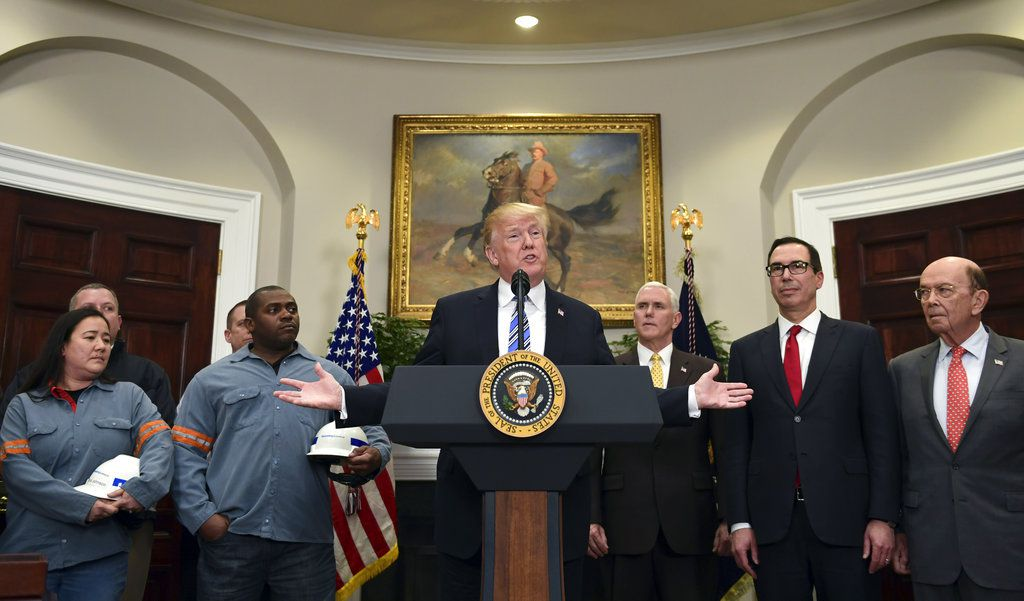President Donald Trump, center, speaks in the Roosevelt Room of the White House in Washington, Thursday, March 8, 2018, before signing two proclamations, one on steel imports and one on aluminum imports. Standing with Trump are workers, left, Vice Preside